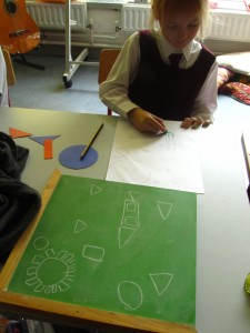 Emma making her shape picture from a plan.